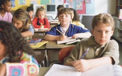 Attentive boy looking up from his desk in crowded classroom