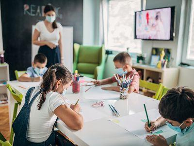 kids wearing masks while drawing