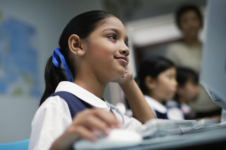 Girl at computer in classroom with other students in background