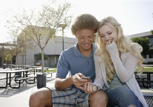 Teen couple looking at cell phone