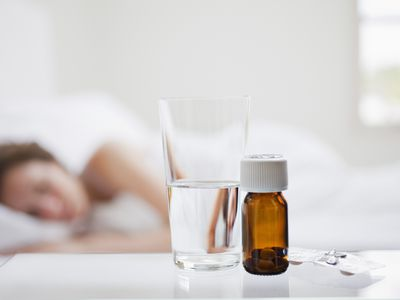 Close up of pill bottle with sick woman in background