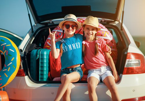 two young girls on the back of a car