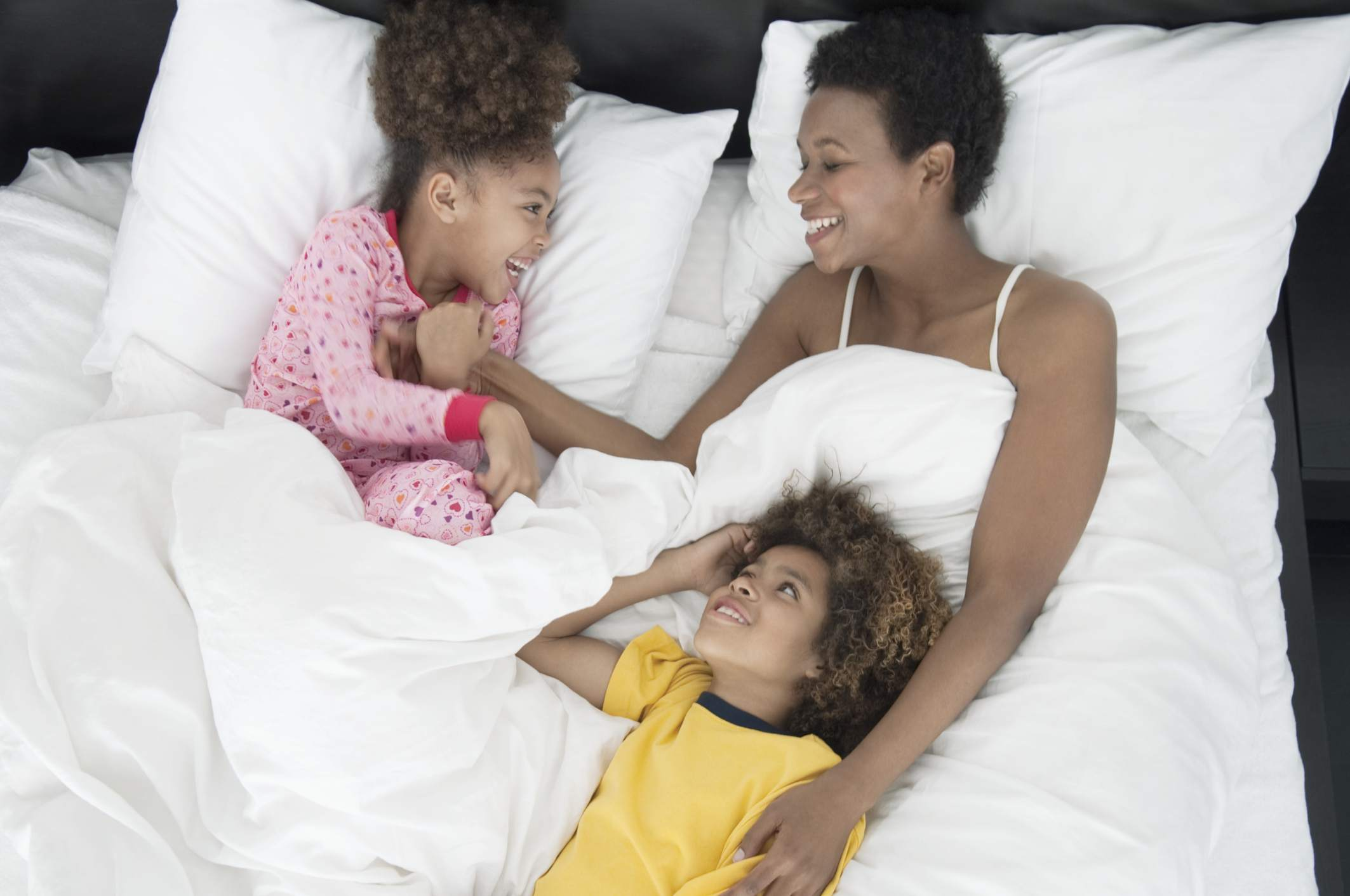 Mother cuddling in bed with her children