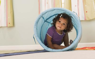 a toddler inside a toy tunnel