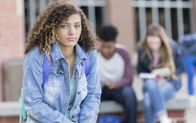 Sad-looking college student with classmates in background