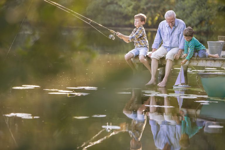 Grandfather and grandsons fishing and playing with toy sailboat at lake