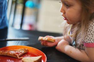 child eating peanut butter sandwich