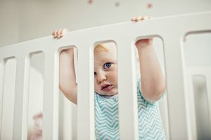 Baby standing in a white crib.