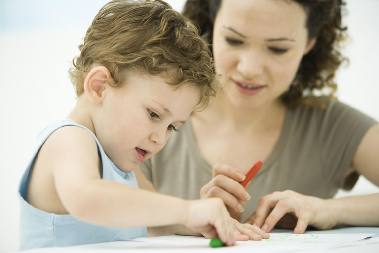 Mother and son sitting together, coloring with crayons