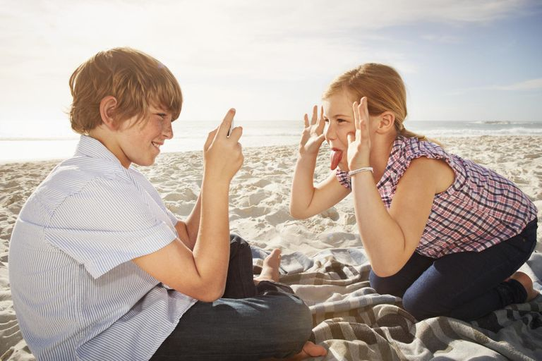 Boy taking picture of girl with smart phone