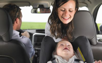 Mother Watching Baby In Car Seat