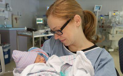 Preemie mom holding preemie baby in NICU