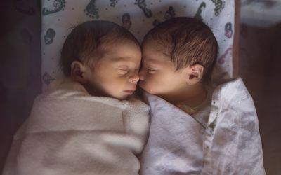 Newborn Twins in Hospital Sleep Together in Plastic Crib