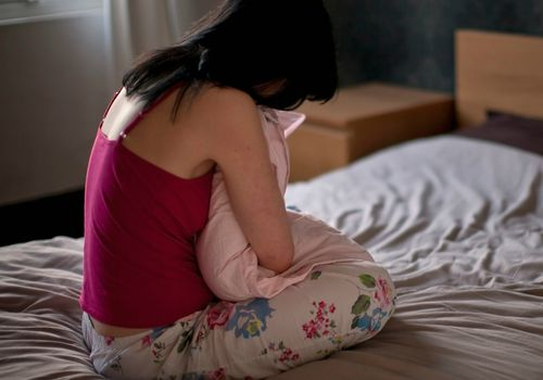 Upset woman hugging pillow on bed