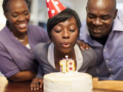 African female teenager blowing out the candles on her 18th birthday cake, surrounded by her family
