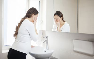 A pregnant woman looking nauseous standing at the bathroom sink