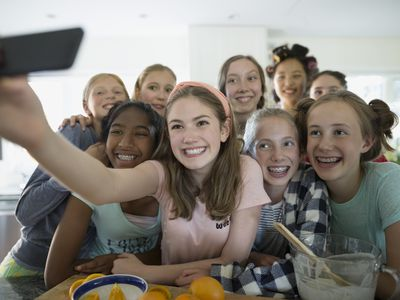 Girls taking a selfie while making breakfast after a slumber party
