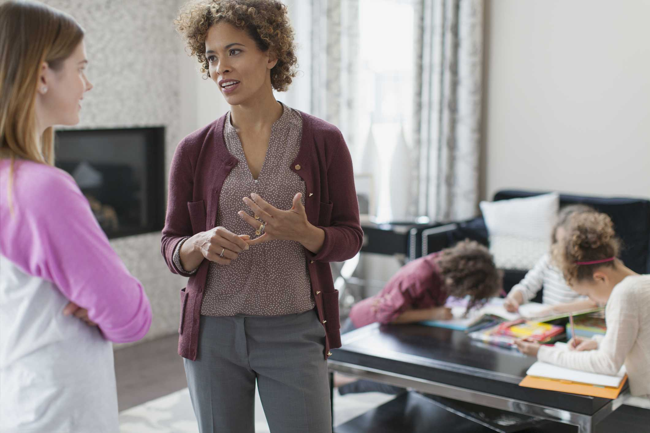 Mother talking to babysitter while kids color in background