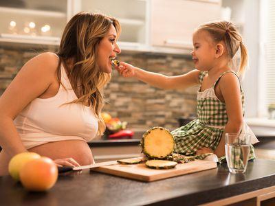 Little girl feeding pineapple to pregnant mom