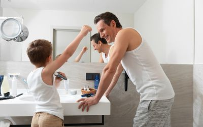 child and dad putting on deodorant