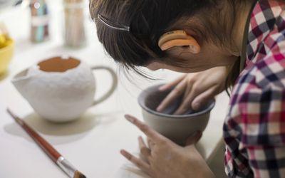 teenage girl with hearing aid doing ceramics