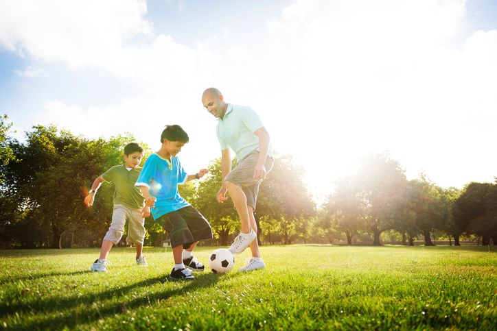 adult man playing soccer with two boys