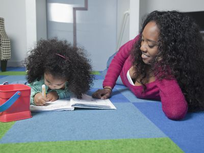 Mixed race mother watching daughter color