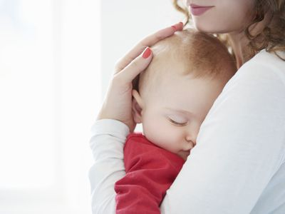 baby sleeping in the arms of mother