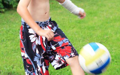 Boy wearing cast on arm kicking a soccer ball