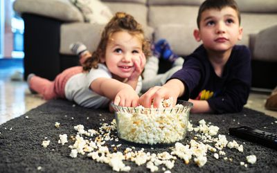 Siblings watching a movie while eating popcorn