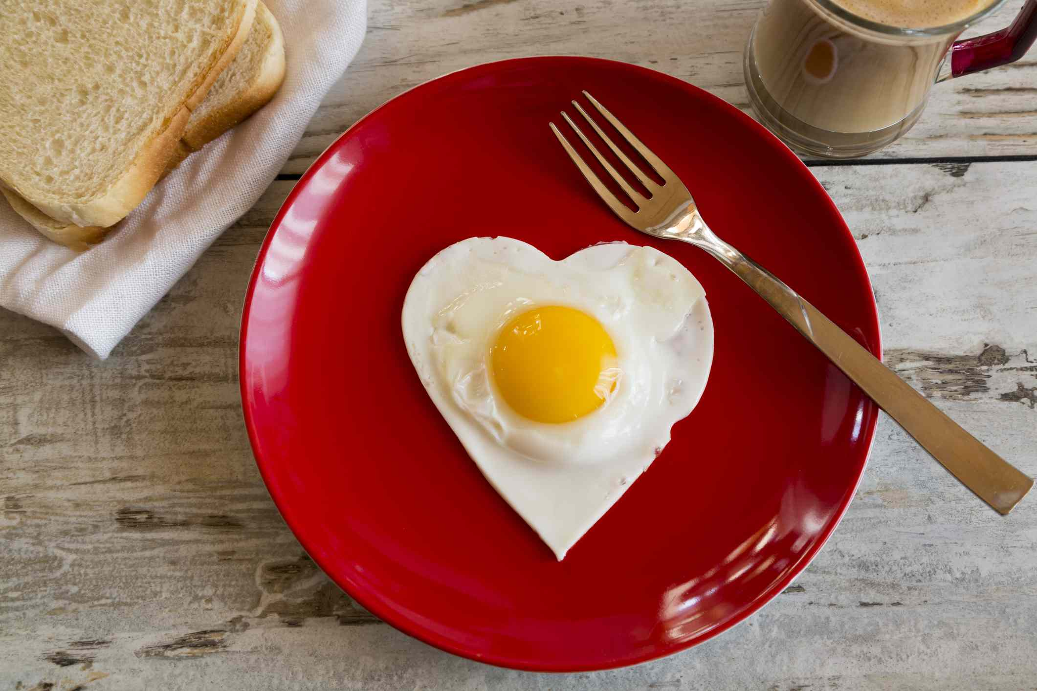 Heart-shaped fried egg on a red plate