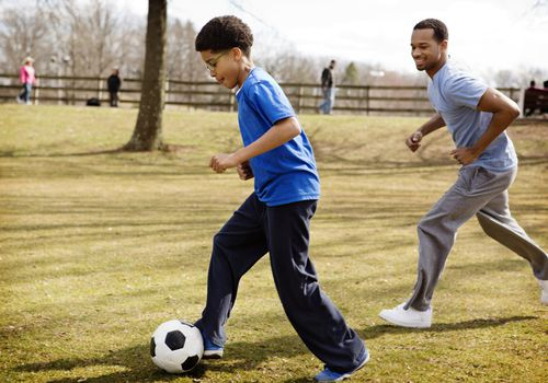 father playing soccer with son