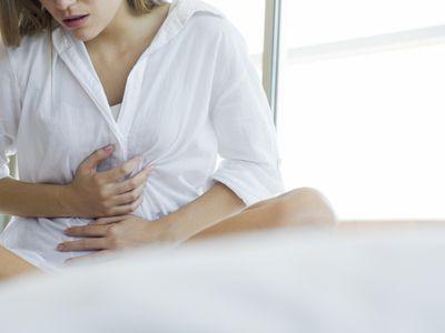 Woman clutching both hands over abdomen