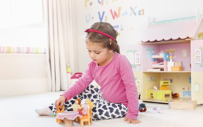 young girl playing with dolls house in bedroom.