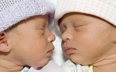 Twins sleeping in the hospital.