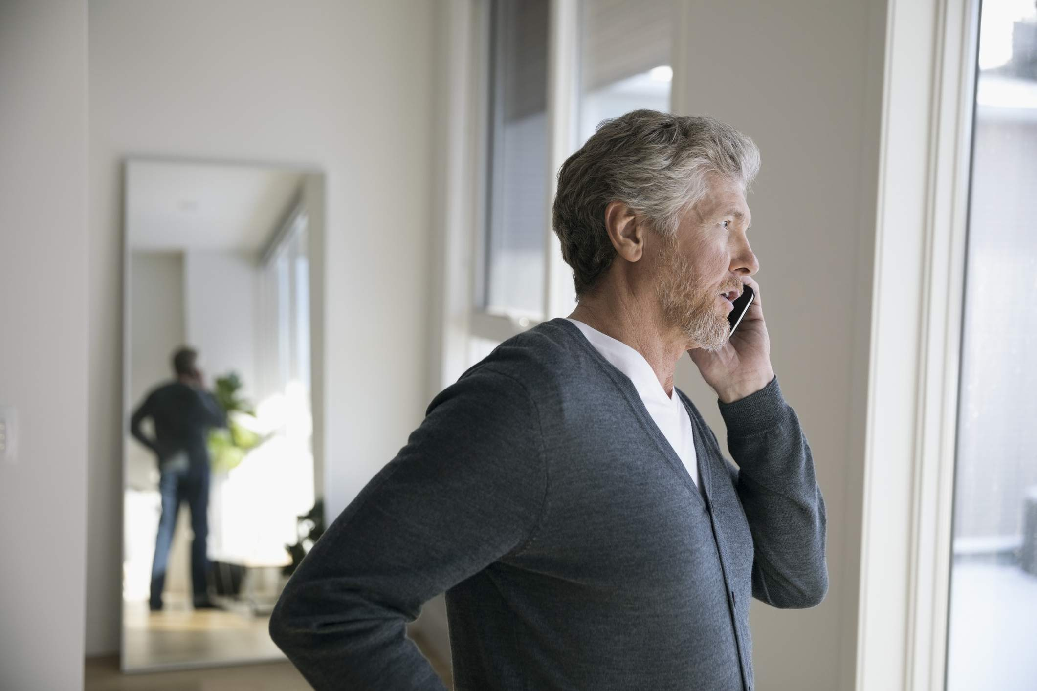 Man talking on cell phone, looking out window