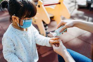 Child in mask applies hand sanitizer