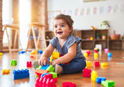 toddler sitting on the floor playing with building blocks