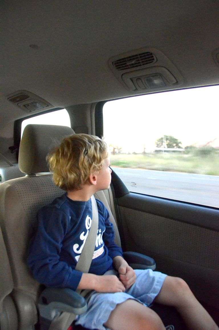 A child sitting in a noback booster seat looking out the window.