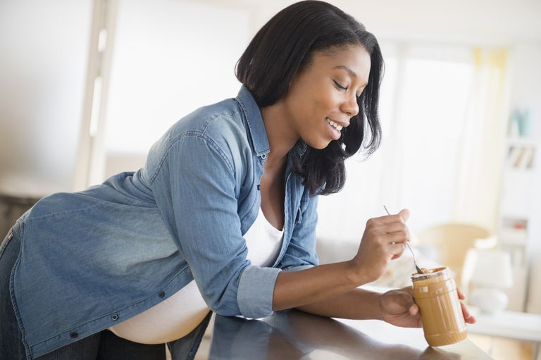 Black pregnant woman eating peanut butter in kitchen