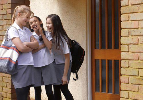 School girls gossiping outside school