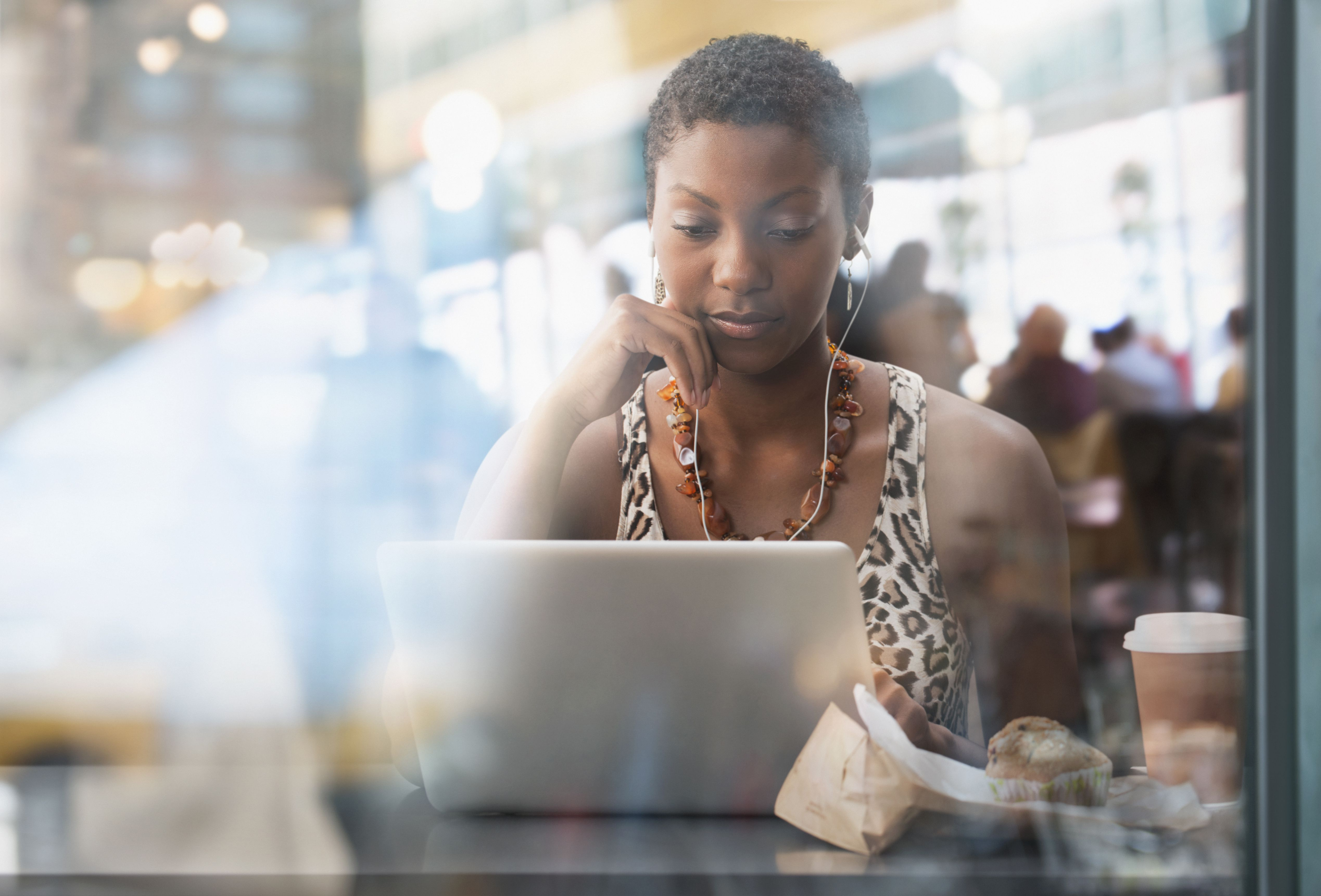 African American woman using laptop in cafe, trying to be sensitive to friends with infertility