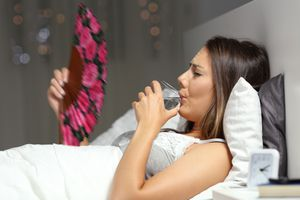 a pregnant woman fanning herself in bed to cope with feeling hot and sweaty