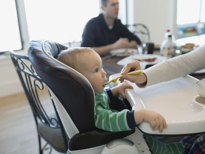 Mother feeding baby boy in high chair