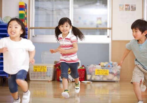 three little children running in play room