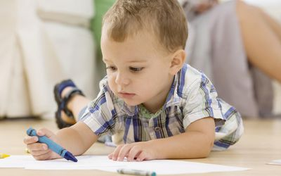 Baby coloring on floor