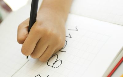 Child's hand writing in notebook