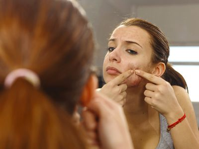 woman popping pimple in mirror