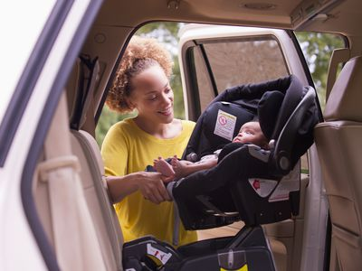 Mother putting baby in car in car seat