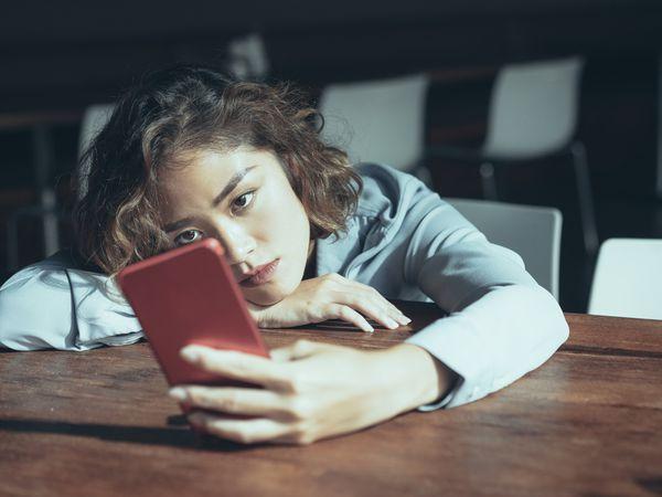 Sad young woman on smartphone